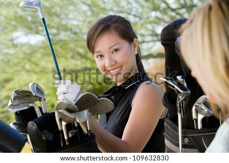 Portrait of a happy young woman picking up golf club from bag - stock photo