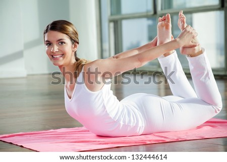 Portrait of a happy young woman practicing yoga exercise called Bow Pose - stock photo