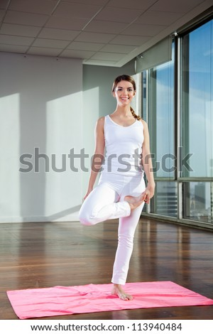 Portrait of a happy young woman standing in Tree pose on mat - stock photo