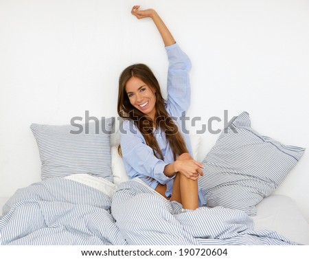 Portrait of a happy young woman waking up in bed and stretching arms - stock photo