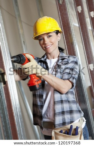 Portrait of a happy young woman worker drilling at construction site