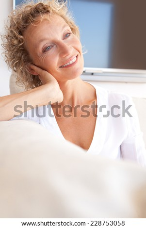 Portrait of a healthy and successful mature professional woman sitting on a sofa at home relaxing, smiling with a flat tv screen in the background. Aspirational beauty lifestyle and home living. - stock photo