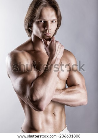 Portrait of a healthy muscular young man on a gray background - stock photo
