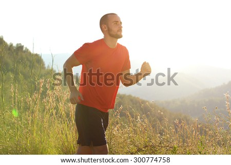 Portrait of a healthy sports man jogging outdoors in nature