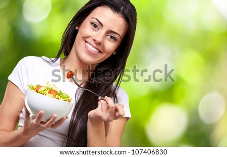 portrait of a healthy woman eating a salad against a nature background - stock photo