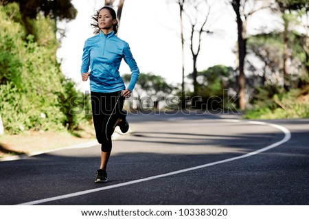 portrait of a healthy woman training for running along a mountain road alone. fitness wellness athlete - stock photo