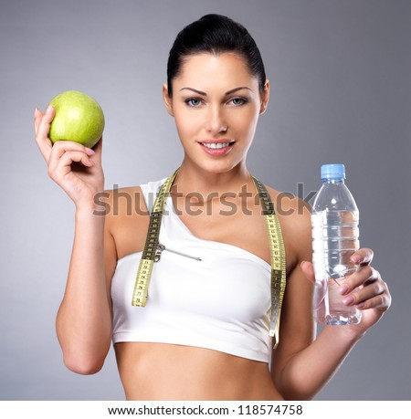 Portrait of a healthy woman with apple and bottle of water. Healthy fitness and eating lifestyle concept. - stock photo