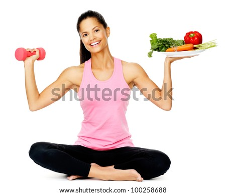 Portrait of a healthy woman with vegetables and dumbbells promoting a healthy fitness and eating lifestyle - stock photo