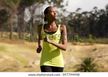Portrait of a healthy young african woman running outdoors  - stock photo