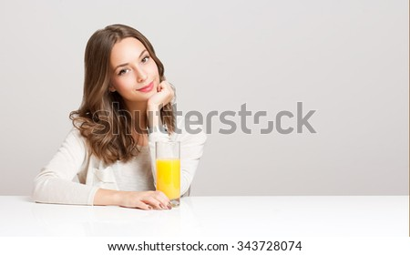 Portrait of a healthy young brunette beauty with glass of orange juice. - stock photo