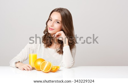 Portrait of a healthy young brunette beauty with glass of orange juice and fruit.
