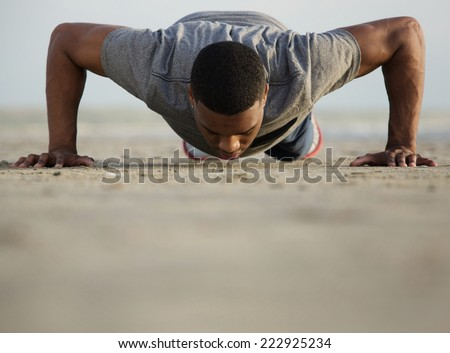 Portrait of a healthy young man doing push ups at the beach  - stock photo