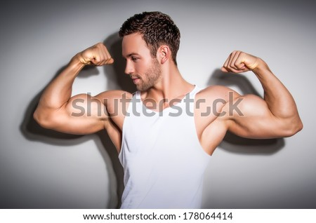 Portrait of a healthy young man showing his arms  - stock photo