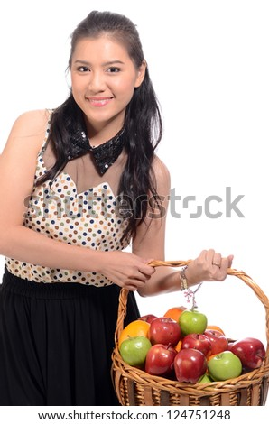 Portrait of a healthy young woman holding basket of fruits over white background.