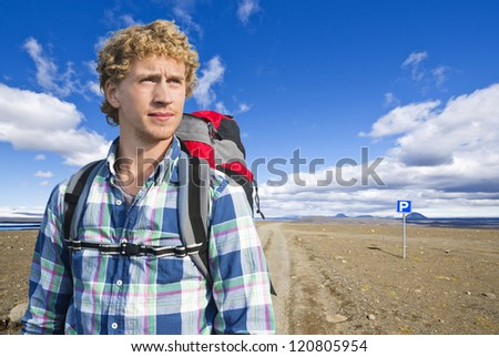 Portrait of a hiker in front of the vast, volcanic tundra landscape of Sprengisandur in Iceland, in the middle of nowhere, in between two major glaciers on the volcanic Mid Atlantic Ridge - stock photo
