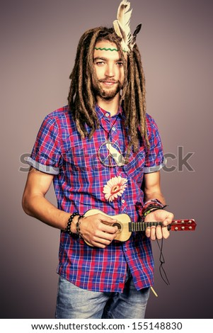 Portrait of a hippie young man playing his guitar. - stock photo