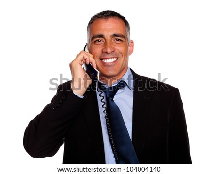 Portrait of a hispanic executive smiling with a phone on black suit against white background