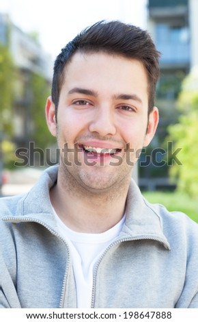Portrait of a hispanic guy in a grey jacket - stock photo