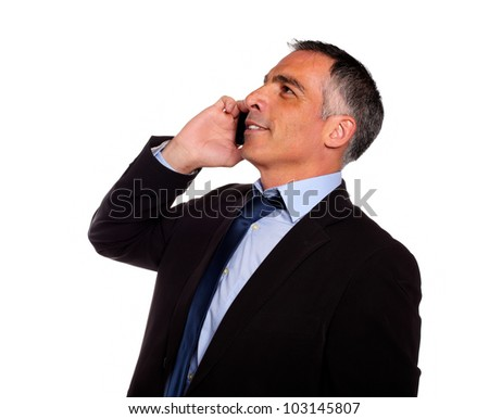 Portrait of a hispanic professional man conversing on mobile and looking up against white background