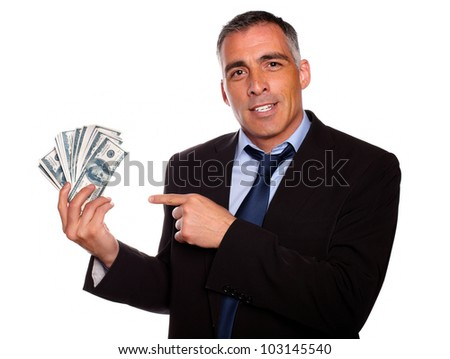 Portrait of a hispanic senior business man holding and pointing  cash dollars on isolated background - stock photo