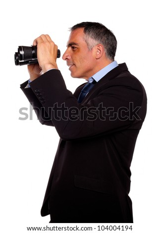 Portrait of a hispanic senior businessman looking forward through binoculars on black suit against white background - stock photo