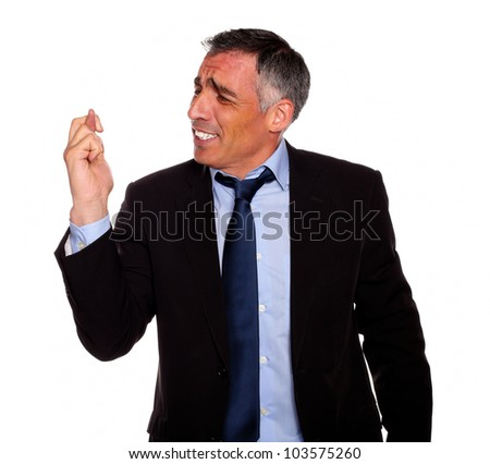 Portrait of a hispanic senior businessman praying for luck on black suit against white background
