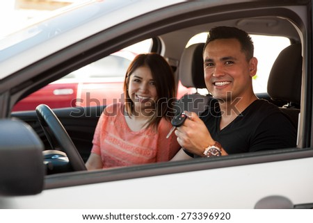 Portrait of a Hispanic young couple excited and ready to ride their new car - stock photo