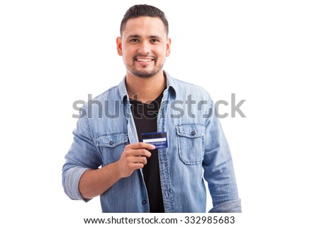 Portrait of a Hispanic young man dressed casually and holding his favorite credit card against a white background