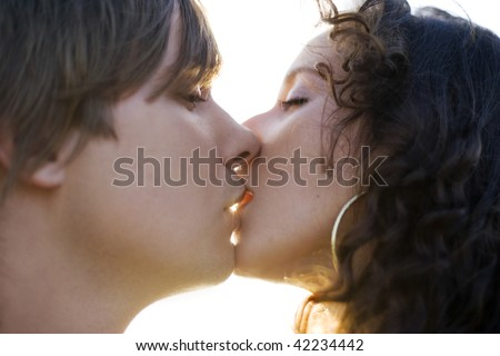 Portrait of a hot young couple kissing (close up).