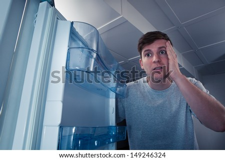 Portrait of a hungry man looking for food in refrigerator - stock photo