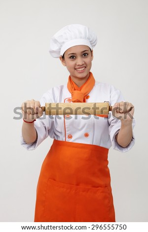 Portrait of a Indian woman with chef uniform holding rolling pin - stock photo