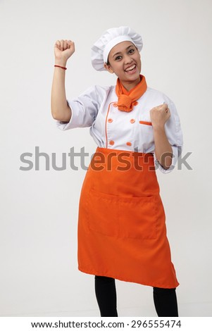 Portrait of a Indian woman with chef uniform with arm's up - stock photo