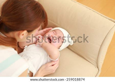 portrait of a Japanese crying baby with mom - stock photo