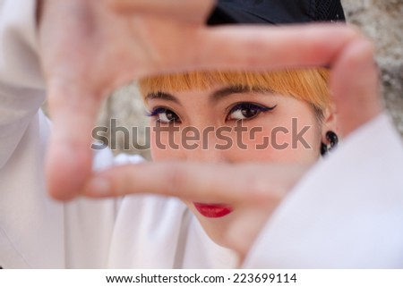 Portrait of a Japanese woman with orange hair as she is framing her face with her own hands. - stock photo