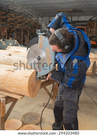 Portrait of a joiner cutting tree trunk with chainsaw in his workshop - stock photo