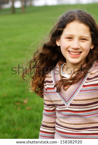 Portrait of a joyful and active young girl child with long red curly hair, running in a green grass field in a park during an autumn sunny day, wearing a stripy jumper outdoors. - stock photo