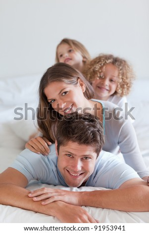 Portrait of a joyful family lying on each other in a bedroom