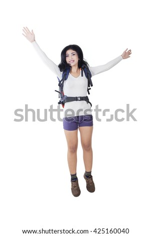 Portrait of a joyful female hiker jumping in the studio while carrying a backpack, isolated on white background