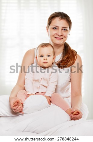 Portrait of a joyful mother and her baby daughter in the bed - stock photo