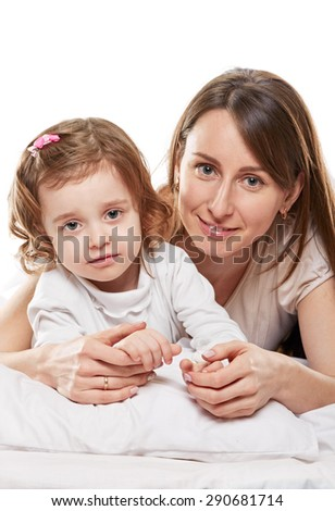 Portrait of a joyful mother and her baby daughter in the bed on white background