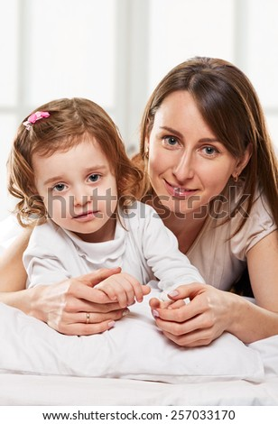 Portrait of a joyful mother and her baby daughter in the bed on window background