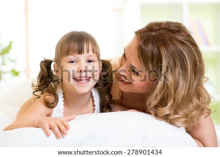 Portrait of a joyful mother and her daughter child lying on bed in bedroom - stock photo