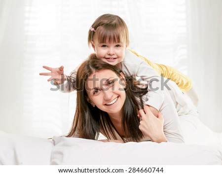 Portrait of a joyful mother and her daughter in the bed on light window background