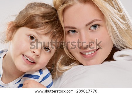 Portrait of a joyful mother and her little daughter in the bed close up