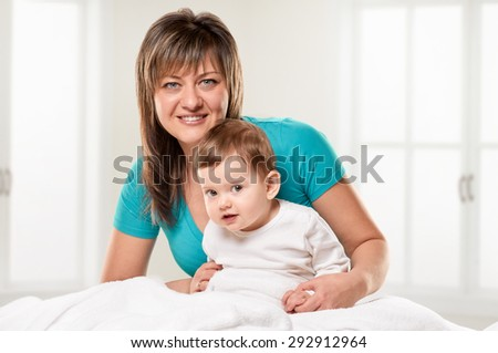 Portrait of a joyful mother and her little daughter in the bed with light window background - stock photo