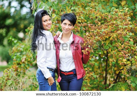 Portrait of a joyful mother with her daughter in the garden - stock photo