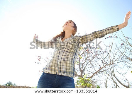 Portrait of a joyful young woman being playful with her arms outstretched and enjoying the sun during a spring day against a sunny sky, smiling. - stock photo
