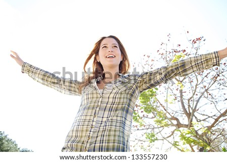 Portrait of a joyful young woman being playful with her arms outstretched and enjoying the sun during a spring day against a sunny sky, smiling.
