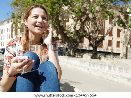 Portrait of a joyful young woman listening to music with her smartphone in the city during a sunny day. - stock photo