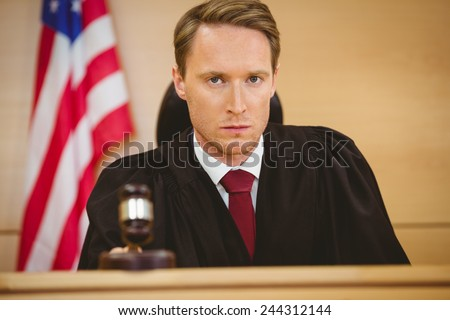 Portrait of a judge about to bang gavel on sounding block in the court room